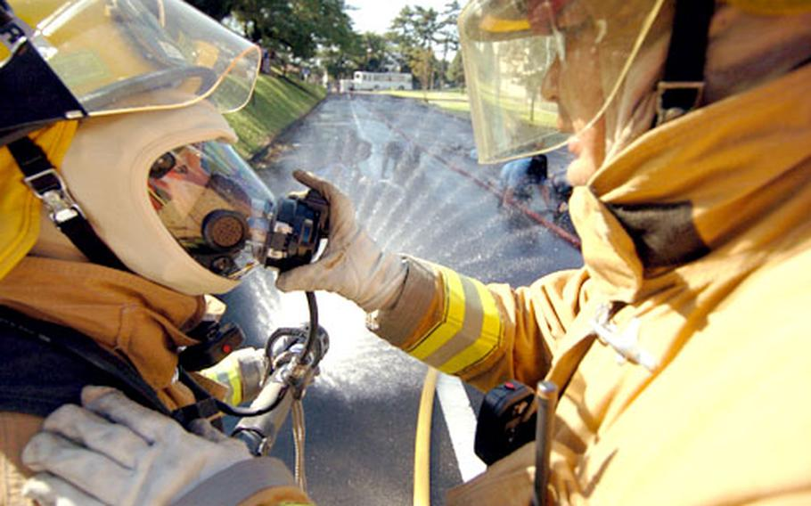 Japanese firemen communicate by using hand signals as they wash down volenteers.