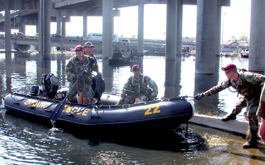 Soldiers from the 82nd Airborne Division's 307th Engineering Battalion come back to land after a house-by-house search for survivors in a flooded section of New Orleans west of downtown Thursday.