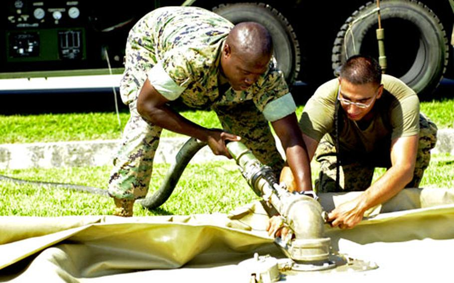 Lance Cpl. Dan Little III, left, a refueler with Marine Wing Support Squadron 172, and Lance Cpl. Warlance Cruz, a bulk fuel specialist with Marine Medium Helicopter Squadron 262, connect a fuel line from a truck to a 3,000 gallon fuel bag on Camp Schwab, Okinawa, on Thursday.