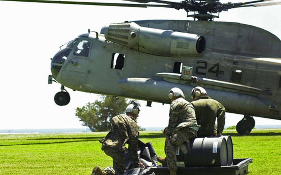 Bulk fuel detachment members from Marine Medium Helicopter Squadron 262 sit on some of their gear while a CH-53 manuevers to drop the rest of their supplies.