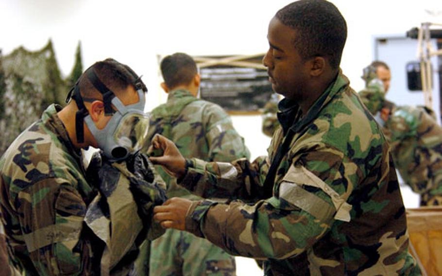 Staff Sgt. James Boyd helps remove gas masks during an Operation Readiness Exercise on Yokota Air Base, Japan, on Saturday. The exercise runs through Friday.