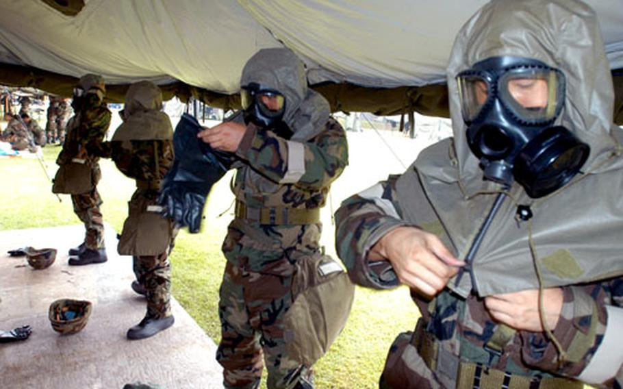 Members of the 15th Company, Korean Service Corps don nuclear, biological and chemical protective gear during common-tasks testing at Camp Red Cloud on Friday.
