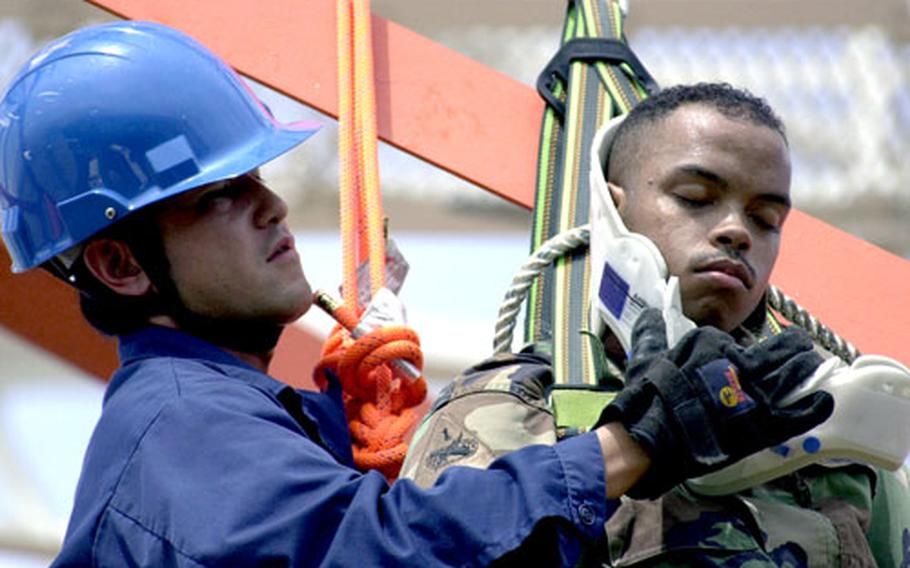 Army Sgt. David Gonzalez, right, is put in a neck collar by Marine Corps Base Firefighter Yogi Manabu during Friday's tower rescue drill on Camp Foster.
