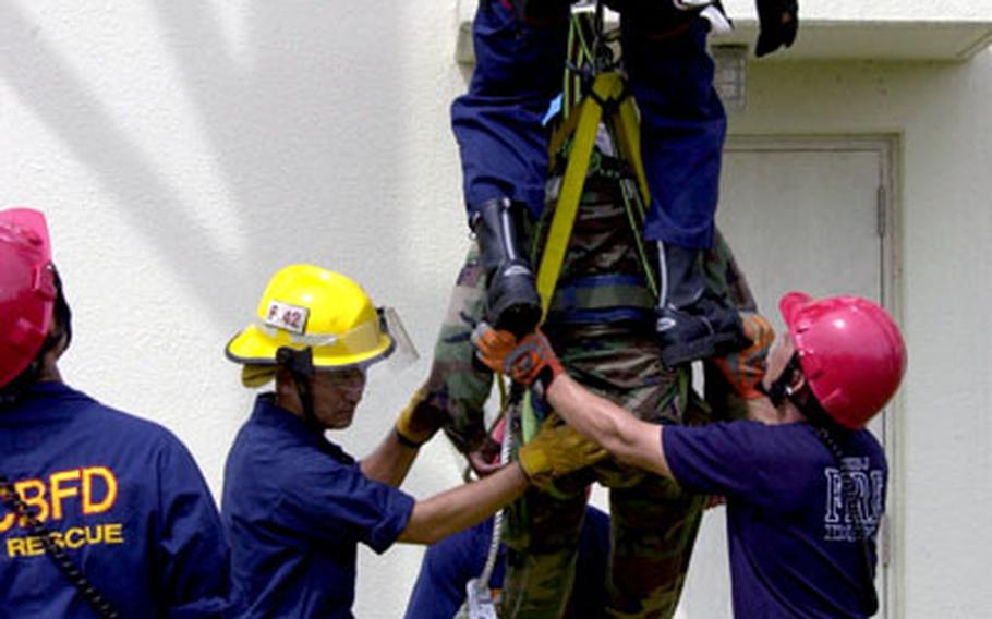 """Marine Corps Base firefighters help guide a """"victim"""" onto a strectcher during the drill."""