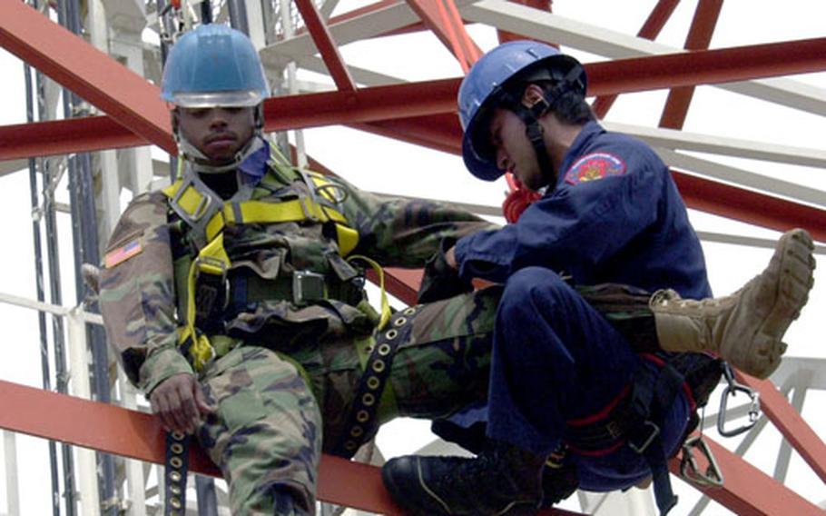Yogi Manabu, right, puts a safety harness on Army Sgt. David Gonzalez.