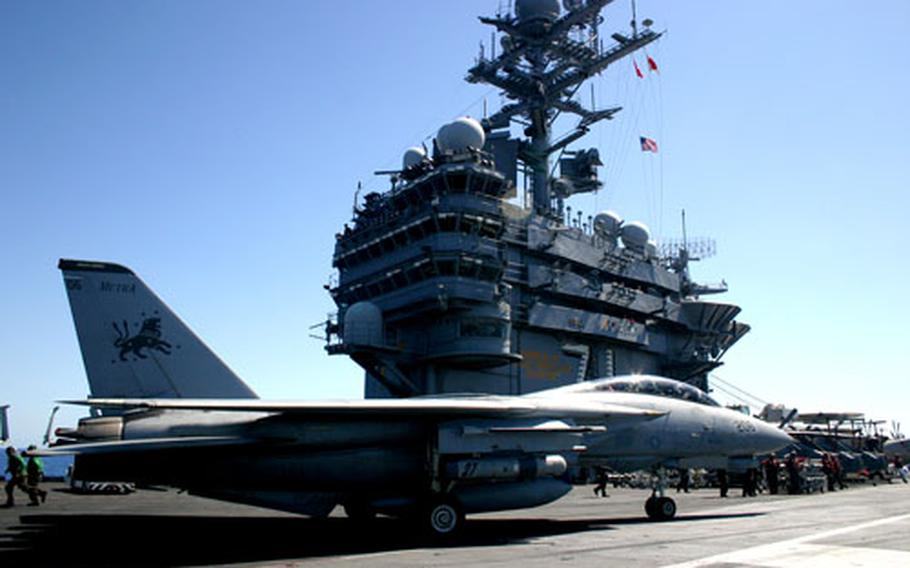 """An F-14 Tomcat taxis by """"the island"""" of the USS Theodore Roosevelt on Saturday after landing moments earlier. The Tomcat will retire for good after Carrier Strike Group 2, led by the Roosevelt, returns next spring after a roughly six-month deployment to the Persian Gulf."""