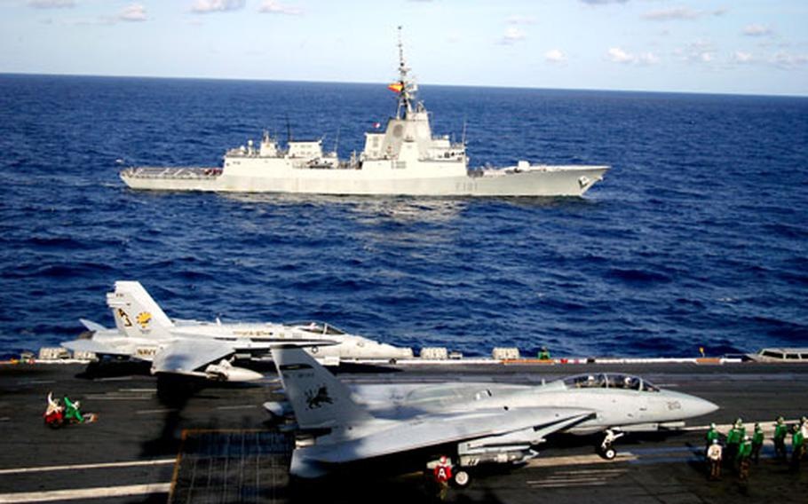 An F-14 Tomcat, foreground, and an F/A-18 Hornet prepare to launch from the deck of the aircraft carrier USS Theodore Roosevelt on Sunday. In the background is the Spanish frigate Alvaro de Bazan.