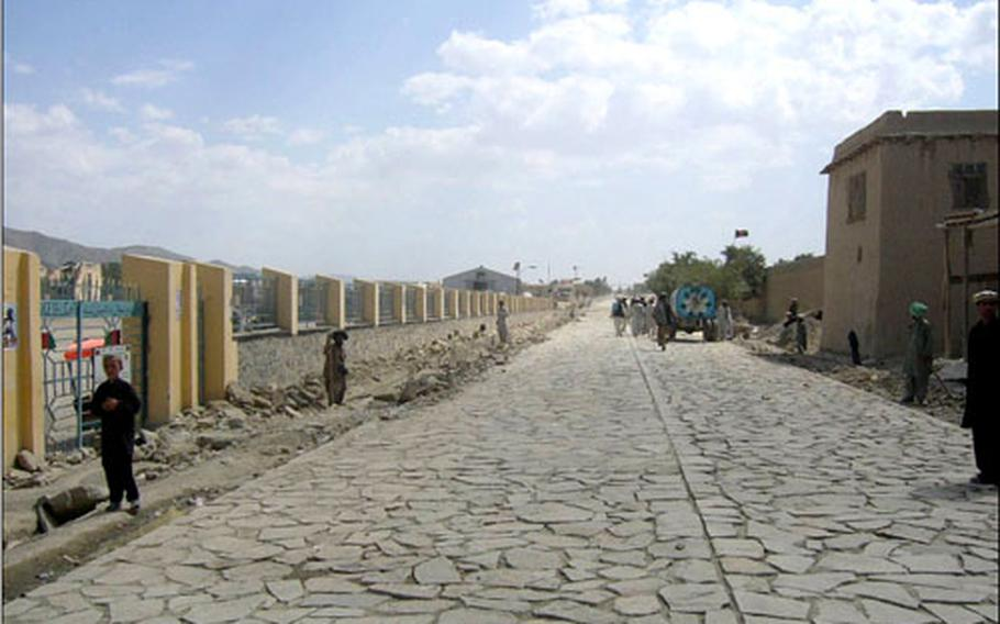 Afghan people use the new cobblestone road in Orgun-E. Coalition forces and Afghan officials celebrated the opening of the 8,200-foot road Sept. 10.
