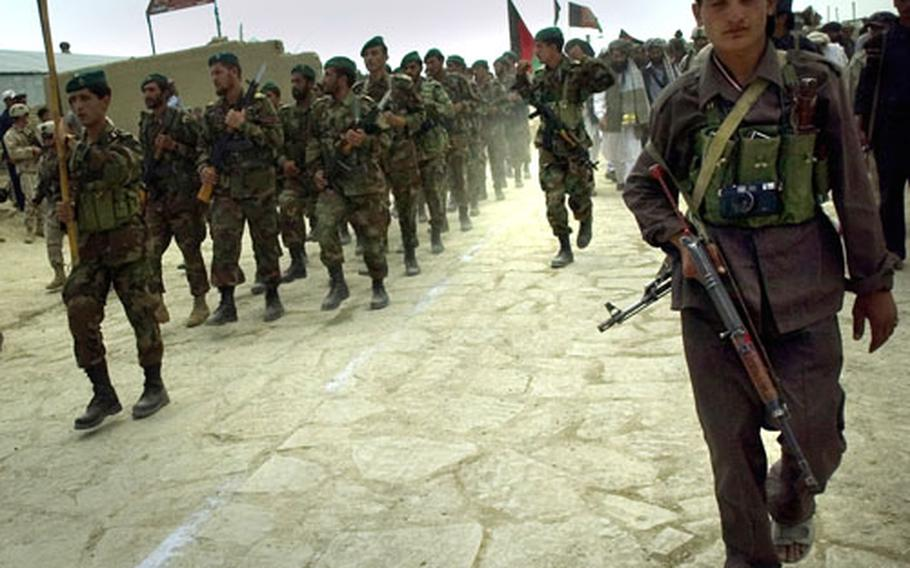 Afghan National Army soldiers march Saturday on the new cobblestone road in the town of Orgun-E.
