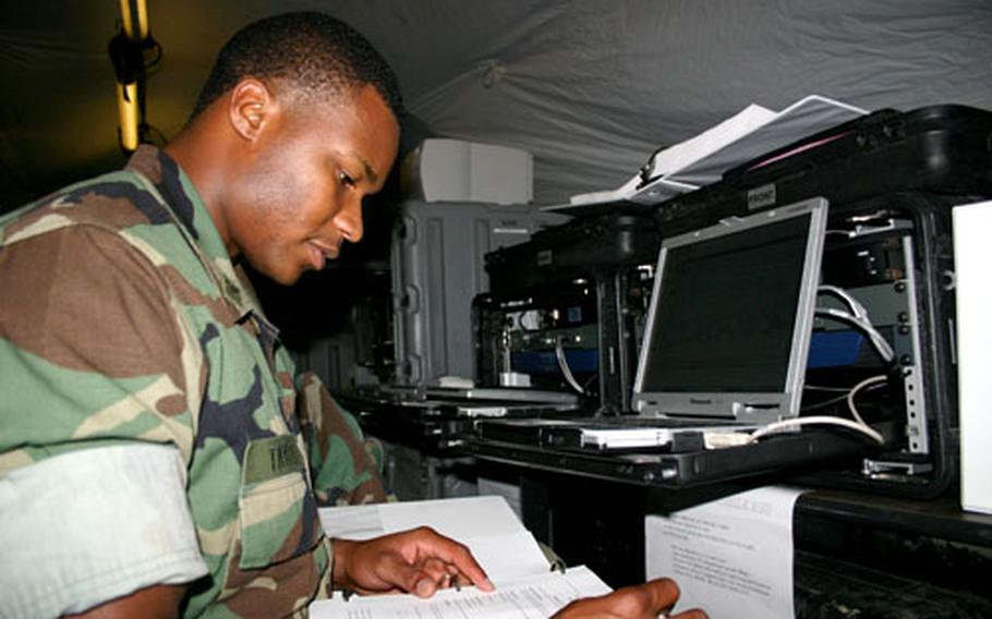 Petty Officer 2nd Class Keion Taylor, of the new for the new TACMOBILE EUR unit, scours a computer manual at NAS Sigonella.