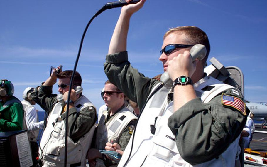 """Landing signal officers aboard the USS Theodore Roosevelt hold up what is called the """"pickle,"""" which lets pilots landing aboard aircraft carriers know whether to proceed in for a landing. If the aircraft is too high or too low, the Landing signal officers squash the signal to alert pilots to wave off a landing."""