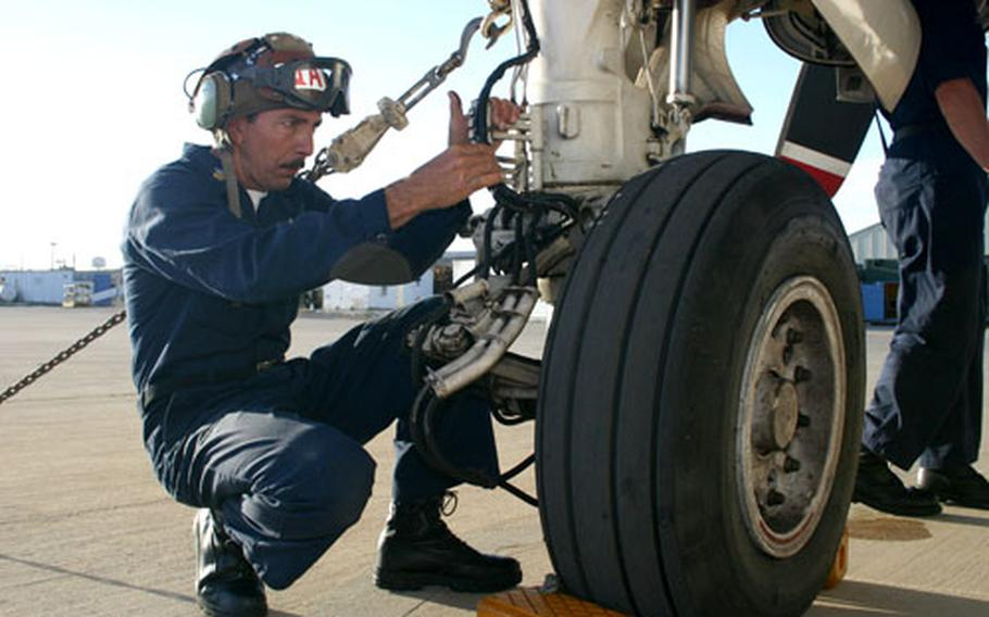 Petty Officer 1st Class Jim Letourneau checks the landing gear on a C-2 Greyhound on Monday at Naval Station Rota, Spain, before the aircraft took off to deliver supplies to the USS Theodore Roosevelt.