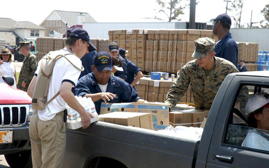 U.S. sailors assigned to the amphibious assault ship USS Bataan, Dutch sailors from the frigate Van Amstel and U.S. Marines load cases of bottled water and Meals, Ready to Eat (MREs) into the bed of a pickup truck at the First Baptist Church near D'Iberville, Miss.