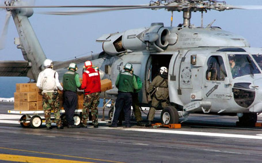 Air Department personnel load MREs onto an HH-60H Seahawk helicopter on the flight deck aboard the USS Harry S. Truman in the Gulf of Mexico on Sept. 5.