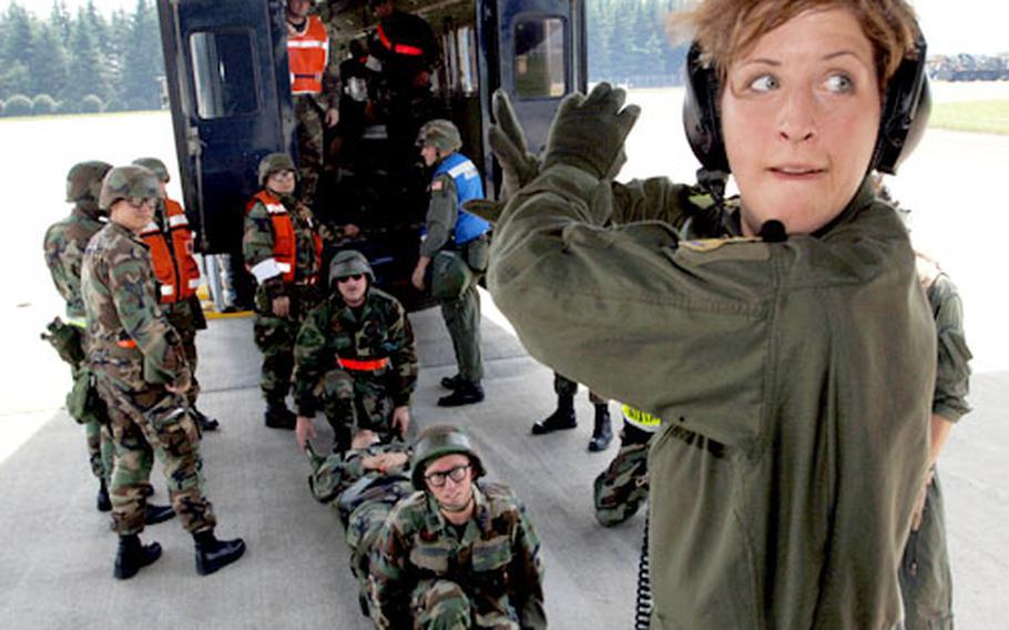 "Capt. Jennifer Ralicki, a flight nurse from the 18th Aeromedical Evacuation Squadron, Kadena Air Base, waits for the green light before evacuating ""injured"" airmen during an Operational Readiness Exercise at Yokota Air Base."