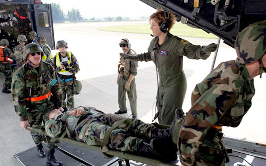 """Capt. Jennifer Ralicki coordinates evacuation of """"injured"""" airmen aboard a C-130 aircraft from 36th Airlift Squadron, Yokota Air Base, during an Operational Readiness Exercise."""