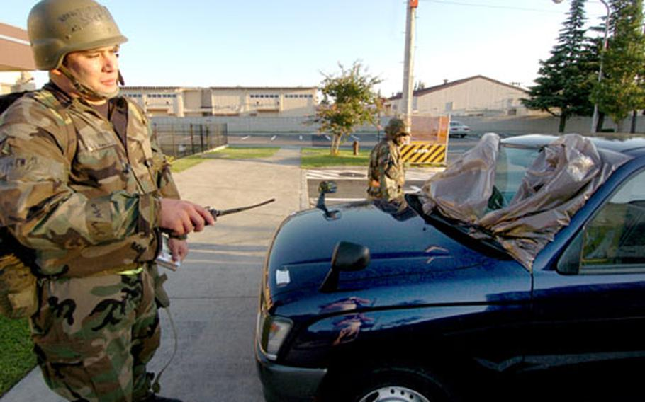 During a training exercise at Yokota Air Base, Staff Sgt. Esequiel King and Staff Sgt. Melvin Holmes search a truck to see if it has been contaminated.