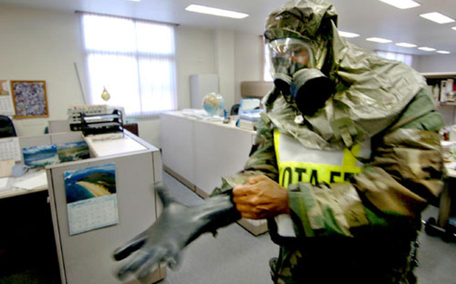 Master Sgt. Karl Logan dons rubber gloves during a training exercise at Yokota Air Base.