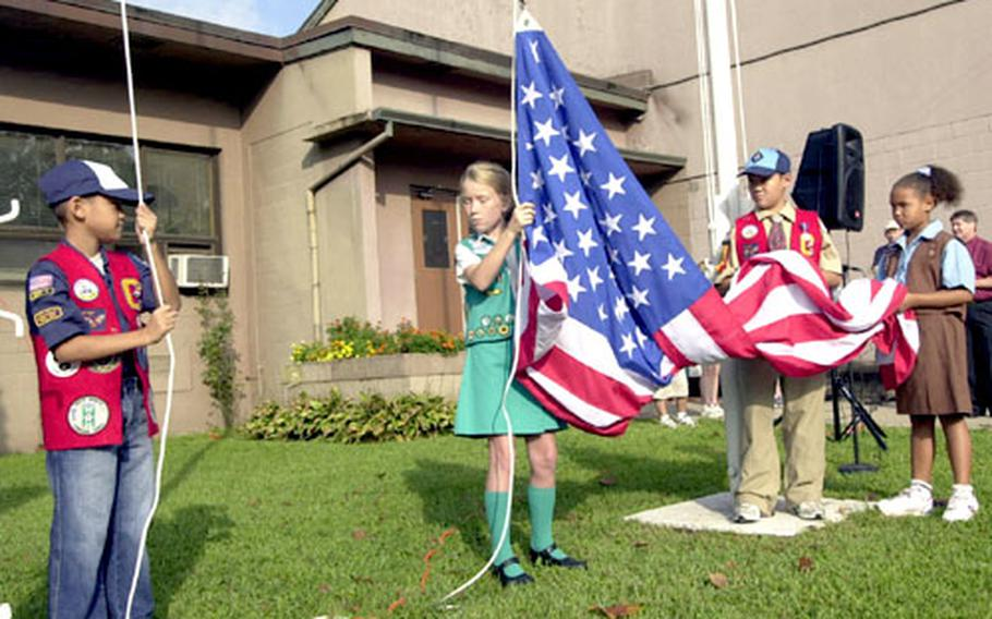 """From left, Aaron Garduna, Savannah Panton, Marc Garduno and Sydney Caldwell raise the American flag at Seoul American Elementary School to kick off a Wednesday morning celebration in honor of the anniversary of the writing of """"The Star-Spangled Banner."""""""