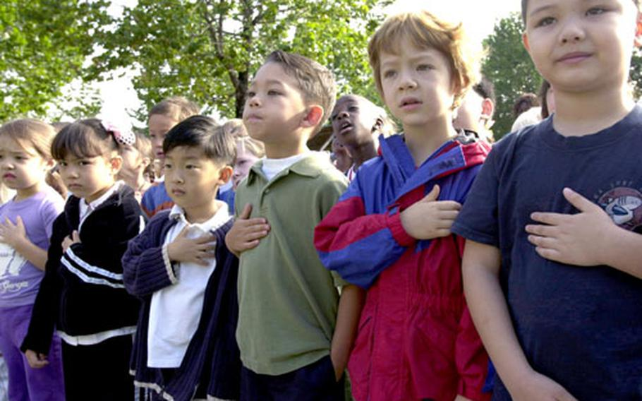 Students recite the Pledge of Allegiance during the ceremony at Seoul American Elementary School.