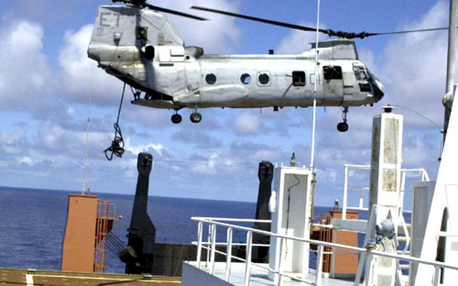 A rope is tossed out the back of a CH-46 Sea Knight helicopter from Marine Medium Helicopter Squadron 262 to simulate Marines fast-roping to the deck of the SS Maj. Stephen W. Pless, a Military Sealift Command ship, during training off the coast of Okinawa on Tuesday.