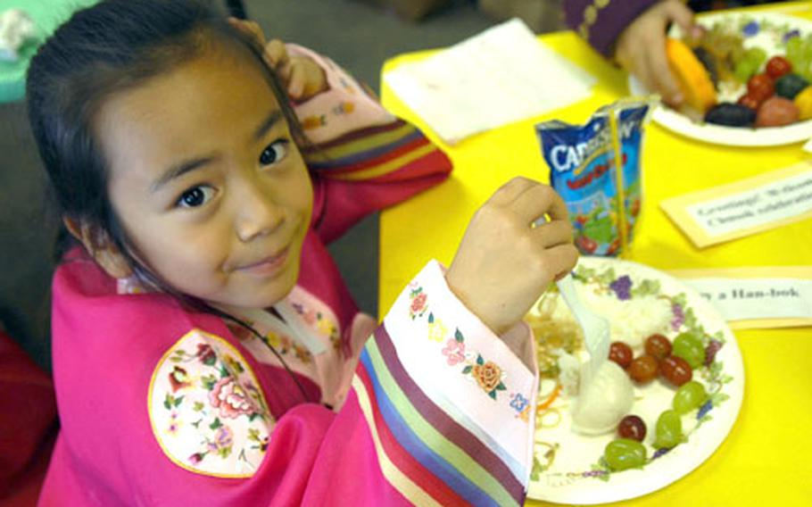 Allison Hill, 6, takes a stab at a songpyeon (stuffed rice cake) Thusday during a potluck Chuseok meal in Rosalind Rutledge's first grade class at Seoul American Elementary School. Millions of families in Korea, like Allison's, will celebrate Chuseok this weekend by traveling to their hometowns and remembering their ancestors.