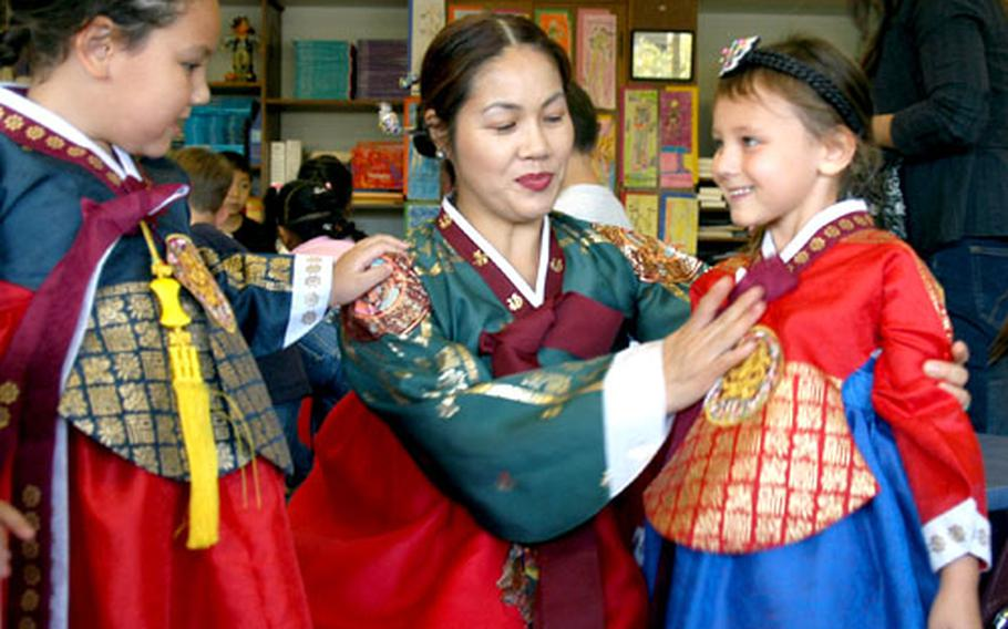 Sookk-young Rinke, middle, straigtens the bow on the hanbok of her younger daughter, Sara, while her older daughter, Rebecca, watches. Rinke was one of many parents who helped Thursday during a Chuseok potluck lunch at Seoul American Elementary School.