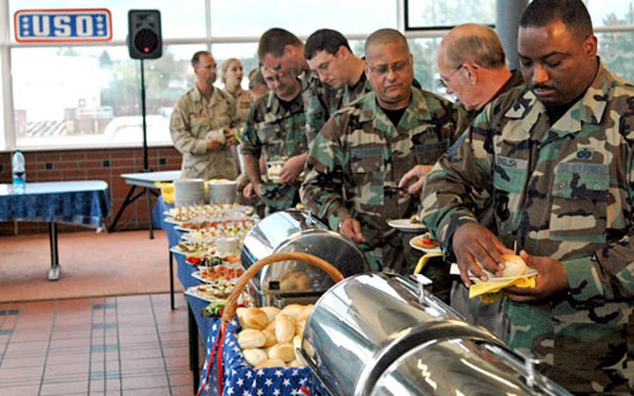 Visitors consider the offerings of a feast spread across four tables at Friday's closing ceremony for the Rhein-Main USO.