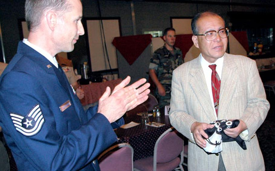 At Marine Corps Air Station Iwakuni's 2005 National POW/MIA Recognition Day program Friday at Club Iwakuni, historian Shigeaki Mori, right, told of his research into the stories of about 20 Allied prisoners of war killed by the blast and aftermath. Air Force Tech. Sgt. Chris Valgardson, left, is chairman of the POW/MIA event.