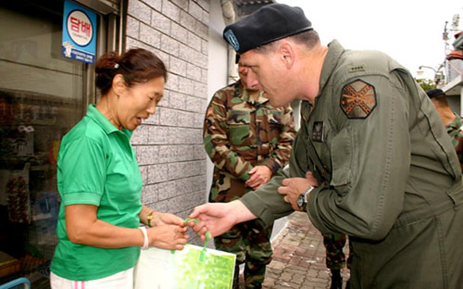 Near Walker Army Heliport in Daegu, South Korea, on Thursday, heliport commander Chief Warrant Officer 4 Brian Parrotte hands a Chuseok holiday gift of frozen oxtail to a local resident. Army officials also gave gifts Thursday to residents outside Camp Carroll in Waegwan.