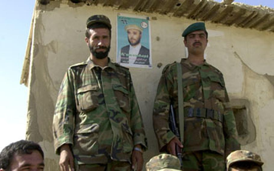 Afghan National Army troops stand next to a campaign poster outside their post in the town of Sayat on Saturday afternoon. The troops will perform security during Sunday's election.