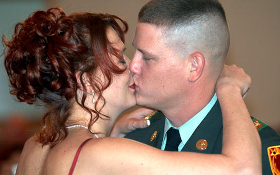 Sgt. Michael Collier and his wife, Dawn, kiss after renewing their wedding vows with six other couples at a ceremony Fridayat the Fliegerhorst chapel in Hanau, Germany.