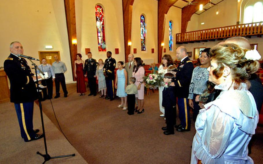 Chaplain (Maj.) H. Vernon McClearn, left, renews the wedding vows of, from left: Jennifer and Anthony Robertson with son Justin; Dawn and Michael Collier; Jill and Robert People; Maty and Dave Richards, with Heather and Clay; Kathy and Michael Harlan with Joshua and Ashton; Kerstin and Michael Thiel (not seen); and Todd (not seen) and Linda Benzschawel at a ceremony at the Fligerhorst chapel in Hanau, Germany, on Friday.