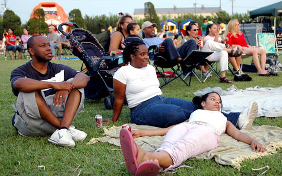 Kei and Skyler Blake, wife and daughter of Sgt. Greg Blake, relax and take in the during the Marine Corps Air Station Iwakuni 2005 Summer Music Festival on Saturday. The Baker family joined hundreds of others on the golf course fairway beside Club Iwakuni for the outdoor concert.