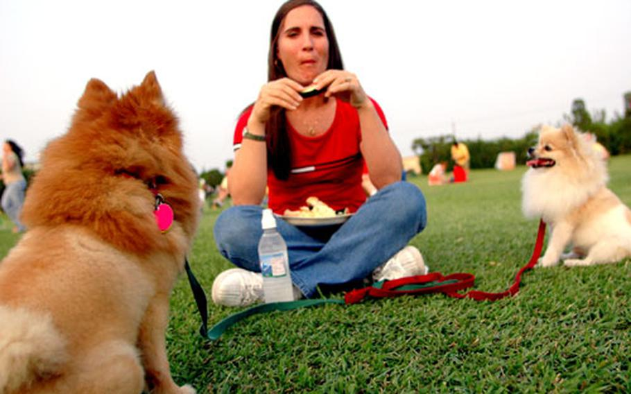 Staff Sgt. Brandi Catledge enjoyed the music and grilled ribs as her two four-legged partners for the afternoon watched and salivated.