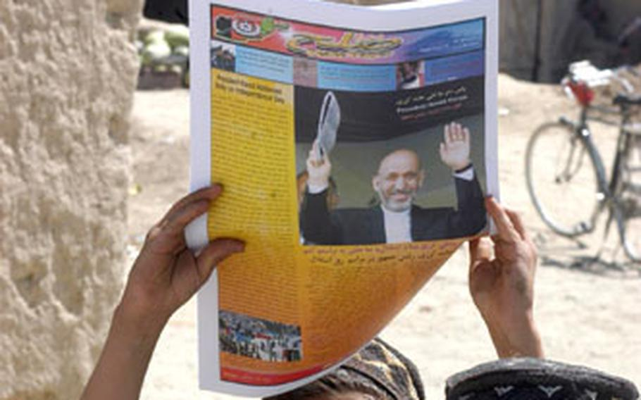 An Afghan youth in Paktika province holds up a paper produced by American forces Saturday that provides information on Sunday's parliamentary elections.