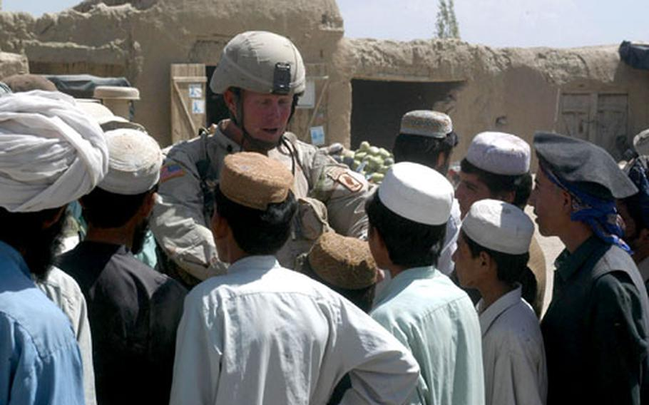 Lt. Col. Tim McGuire, commander of the 1st Battalion, 508th Infantry Regiment, speaks to a group of kids Saturday during a visit to one of a series of villages in Paktika province in Afghanistan, a day before parliamentary elections.