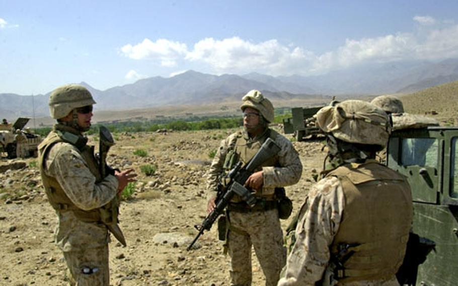 Marine Cpl. Douglas Hampton, left, of the 2nd Battalion, 3rd Marines, recounts the story of hearing rockets insurgents fired his way outside Alishang, Afghanistan, on Sunday. The Marines were providing election security when the incident occurred Sunday morning around 9 a.m.