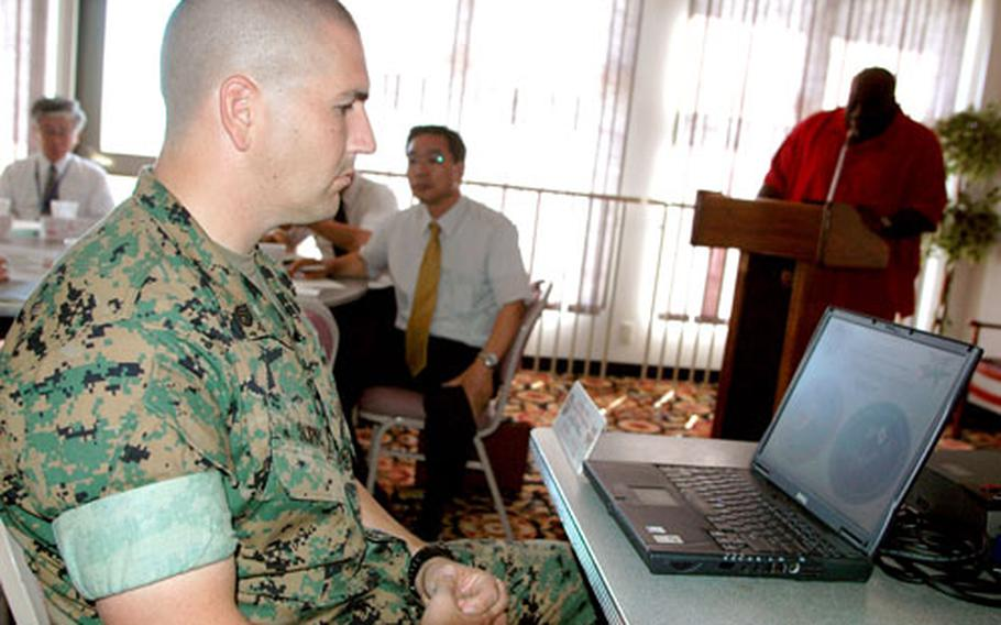 Staff Sgt. Randy Scifo, anti-terrorism and force protection chief at Marine Corps Air Station Iwakuni, controls a Power Point projection coinciding with remarks by Andrew Samuels, antiterrorism and force protection officer.