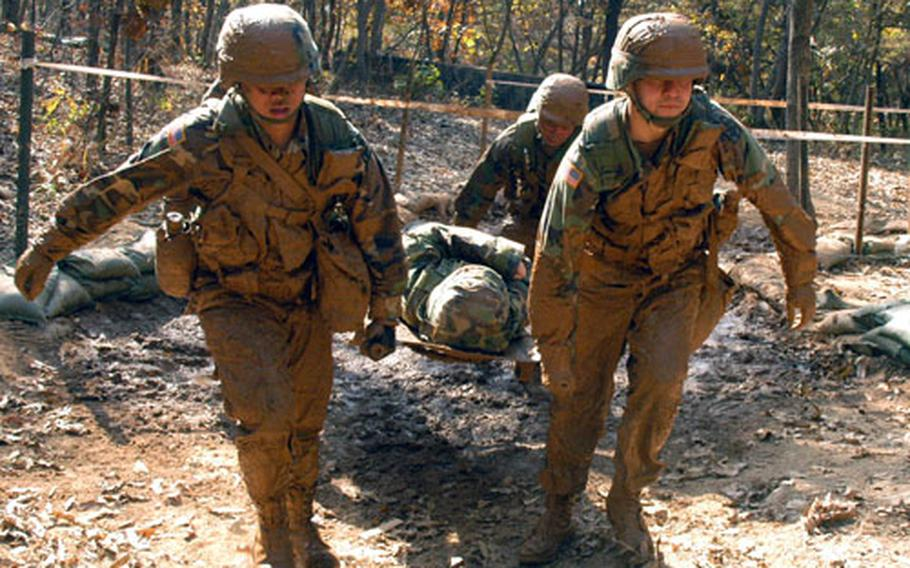 """Soldiers carry a """"casualty"""" through a flooded trench at Warrior Base, South Korea, testing in October 2004. The obstacle is one of many that must be negotiated by stretcher teams composed of candidates attempting to qualify for their Expert Field Medical Badges."""
