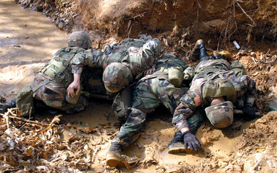 """Soldiers shield a """"casualty"""" from simulated incoming fire during last year's training."""