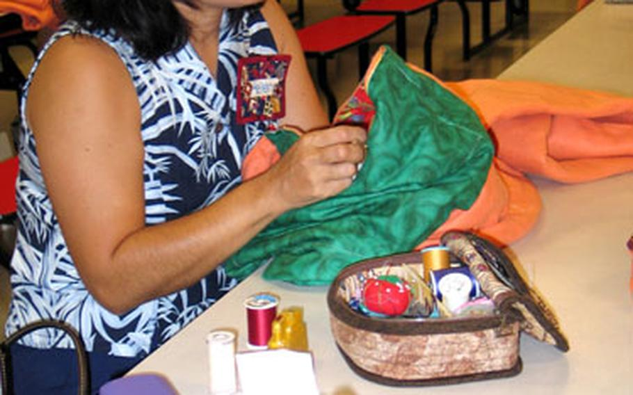 """Helen Davis stitches up a """"quillow"""" for Hurricane Katrina evacuees. The Pacific Patchwork Guild donated 37 of the quilt pillows after a recent quilting bee on Kadena Air Base, Okinawa."""