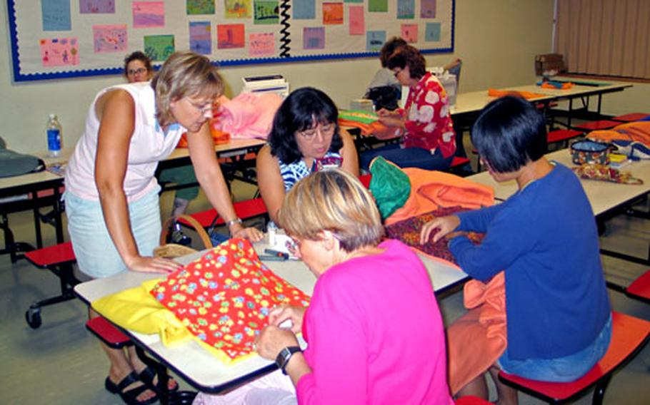 """Members of the Pacific Patchwork Guild prepare """"quillows"""" to donate to Hurricane Katrina evacuees."""