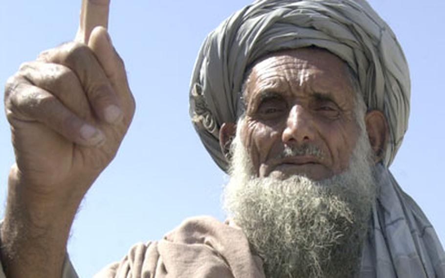 In this 2011 file photo, an Afghan villager near Mehtar Lam displays an ink-stained finger, indicating that he voted.