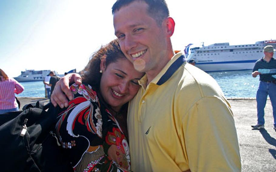 Laura Ingle embraces her husband, Petty Officer 1st Class Kenneth Ingle.