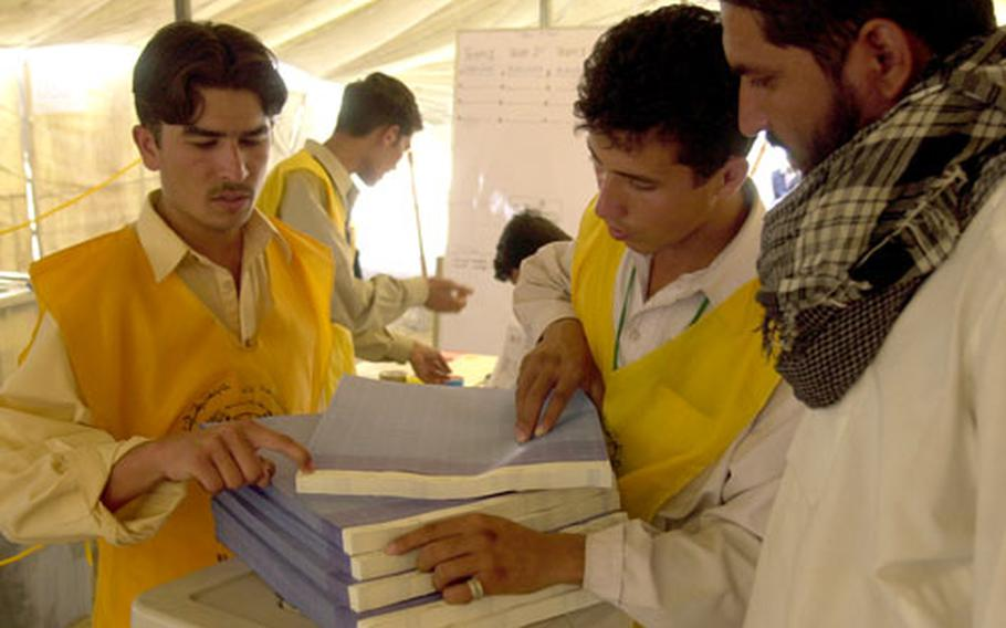 Afghan workers with the U.N.-Afghan Joint Electoral Management Body sort through ballot boxes Tuesday at a compound in Mehtar Lam, Afghanistan.