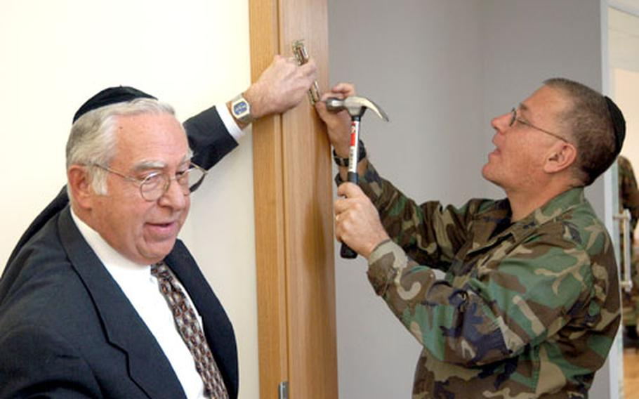 Rabbi David Lapp holds the mezuza as Jewish Chaplain (Capt.) Donald Levy nails it to the door frame of the Jewish sanctuary at the interfaith center at Ramstein. The Mezuza holds a scroll with lines from the sixth chapter of Deuteronomy.