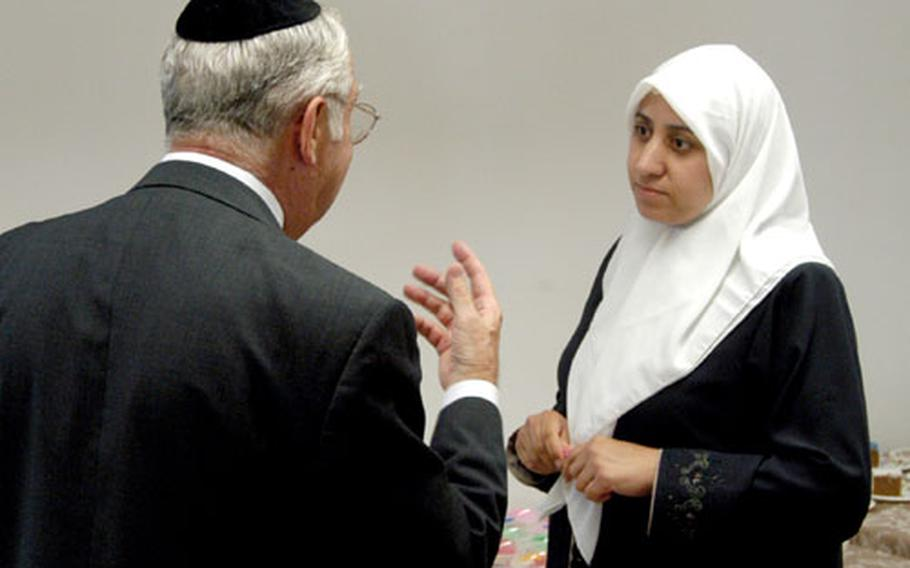 Rabbi David Lapp talks about religion with Widad Issa, a Muslim, following the dedication ceremony of the interfaith center at Ramstein.