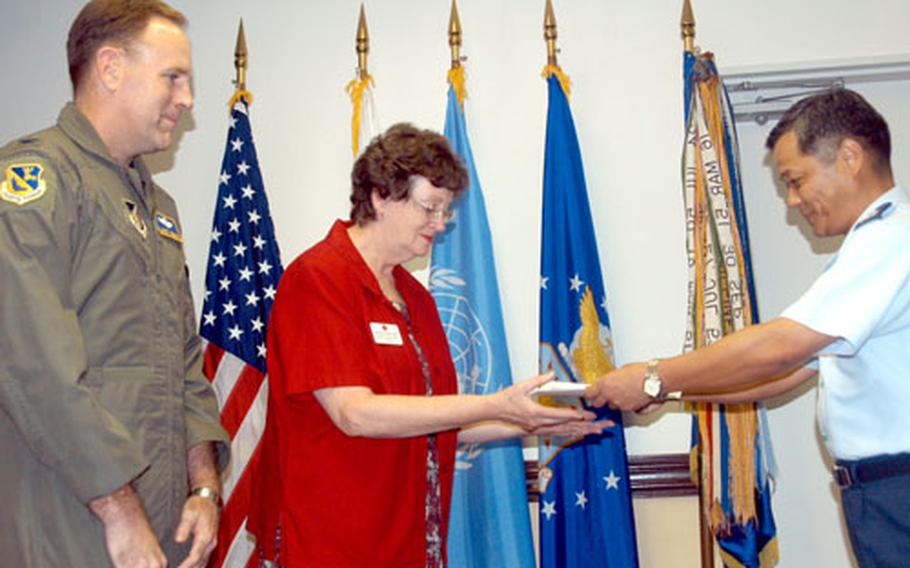 Col. Scott Goodwin, left, the 374th Airlift Wing commander, watches as Col. Osamu Tomita of the Japan Air Self-Defense Force presents a cash donation of 420,000 yen to Jane Dustman, manager of the American Red Cross's Asian-Pacific hub, during a brief ceremony Tuesday at Yokota Air Base, Japan.