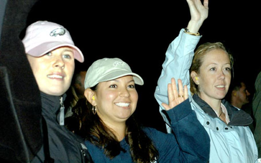 Patty Yeager, right, and two other wives wave goodbye to their husbands as pilots and weapons system officers of the 492nd Fighter Squadron taxi down the runway in F-15 Strike Eagle jets early Wednesday morning for a four-month rotation is support of operations in Iraq and Afghanistan.